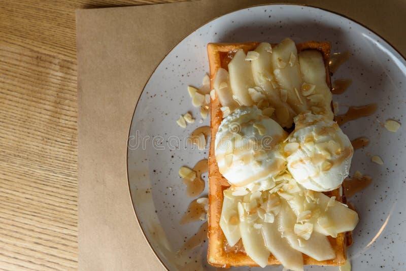 Wunderbares Frühstück oder Nachtisch - Vanilleeis mit Karamellsoße auf belgischer Waffel mit Scheiben der reifen Birne, Spitze stockbilder