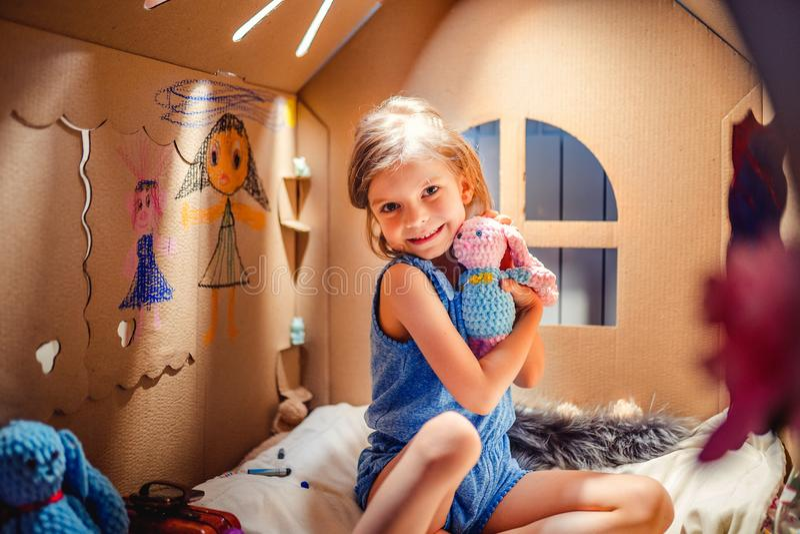 Wunderbares Mädchen mit Spielzeug im Kartonhaus lizenzfreies stockfoto