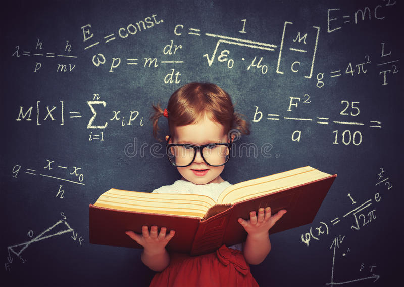 wunderkind little girl schoolgirl with a book from the blackboard with physical formulas stock image