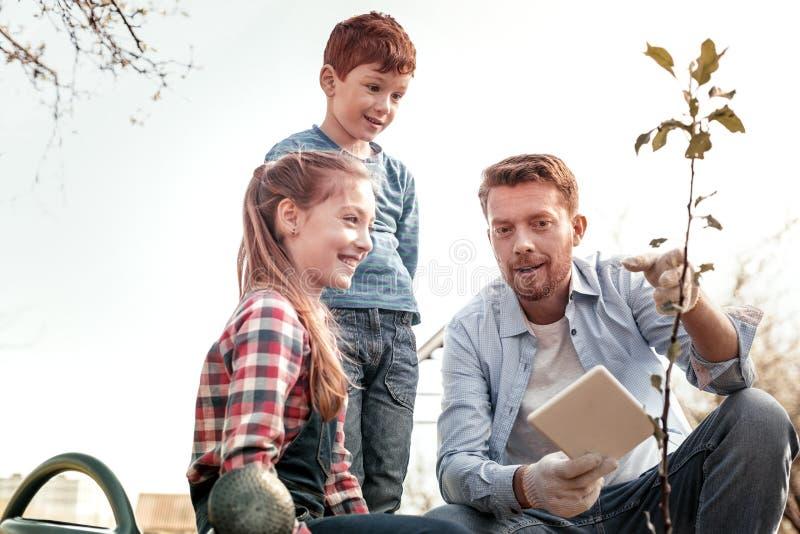 Wundernde lächelnde Kinder, während Vater wie wachsenden Baum erklären stockbild