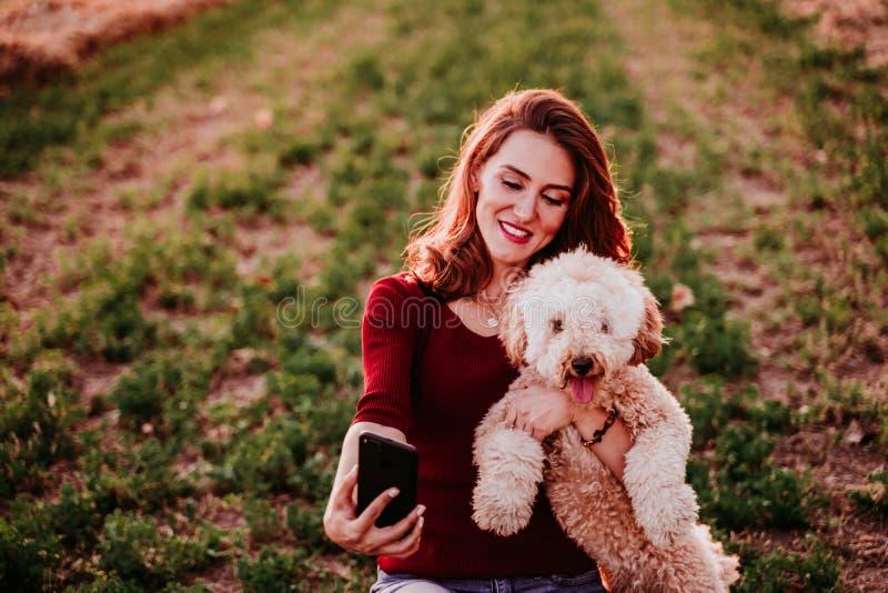 wunderschöne Kaukasierin, die bei Sonnenuntergang mit ihrem Hund selber spielt Mobiltelefon Technologie und Lebensstil lizenzfreie stockfotos
