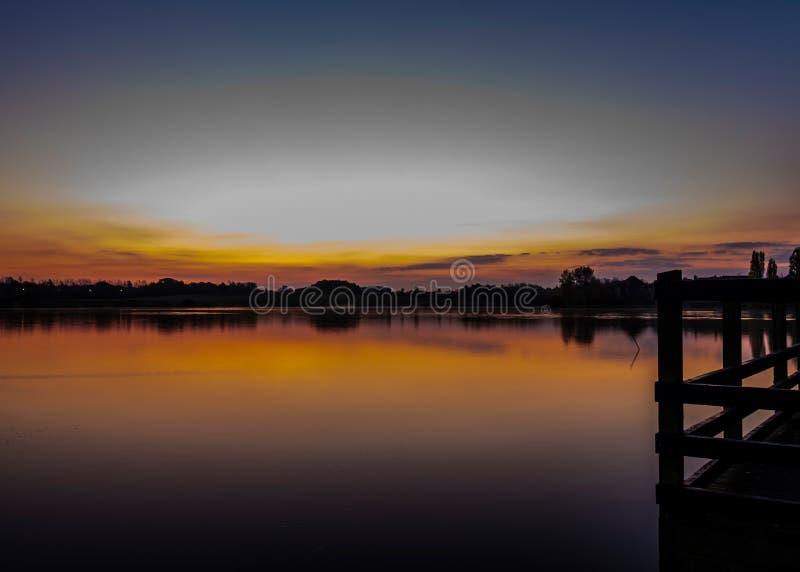 Wunderschöner Sonnenaufgang mit interessanter Reflexion am Furzton Lake, Milton Keynes lizenzfreie stockfotos