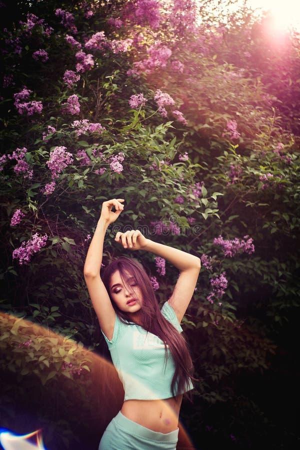 Wundervoller Frühling Ein schönes junges Mädchen genießt Natur und Sonnenlicht unter der blühenden Flieder stockbilder