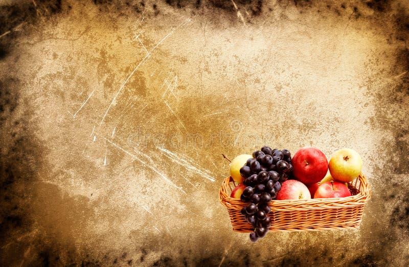 Wundervoller Korb voll des Herbstes trägt auf einem grunge Früchte lizenzfreie stockfotos