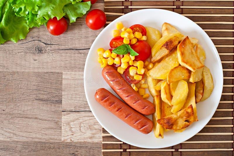 Wurst mit gebratenen Kartoffeln und Gemüse lizenzfreie stockfotografie
