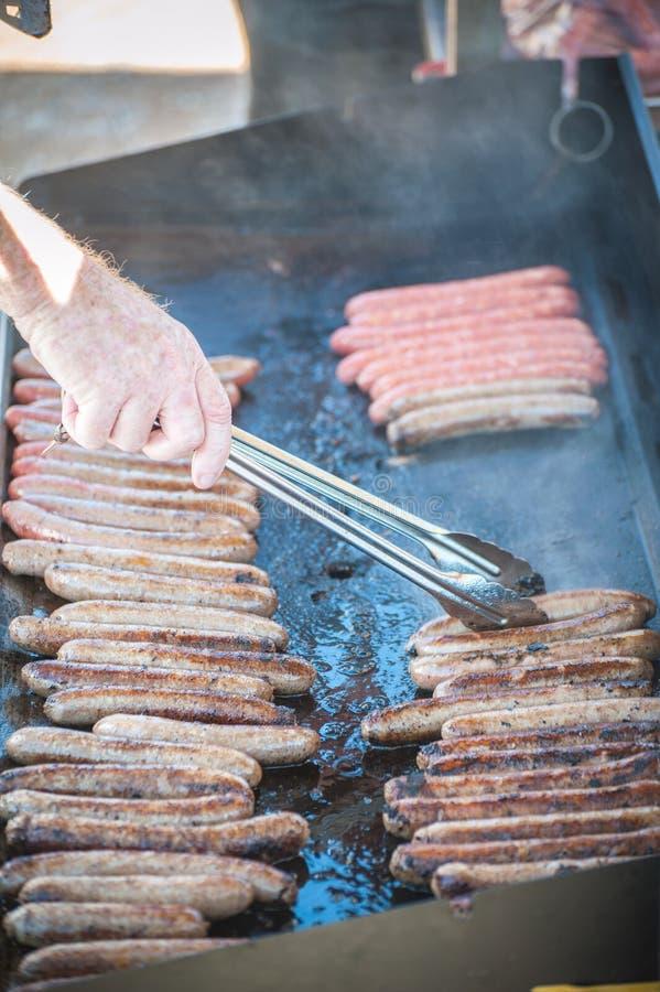 Wurst zischen das Kochen an einem Grill stockfotografie