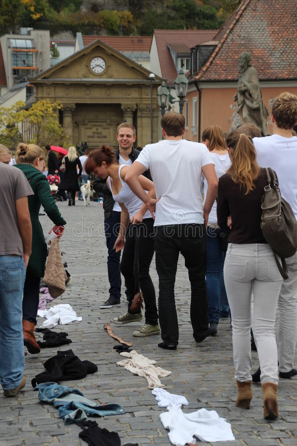 Wurzburg student games. Freshmen students at the University of Wurzburg, Germany make a chain of clothes on the pavement of Alte Mainbrucke, as part of a stock image