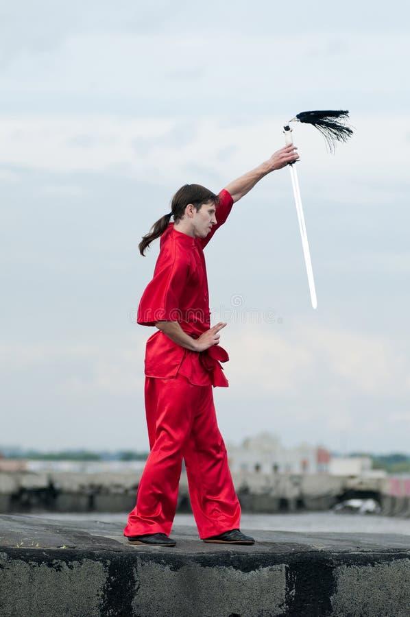 Wushoo man in red practice martial art. Shaolin warriors wushoo man in red with sword practice martial art outdoor. Kung fu stock photos
