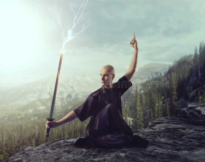 Wushu master with blade, lightning control. On the top of mountain, martial arts. Man in black cloth poses with sword royalty free stock image