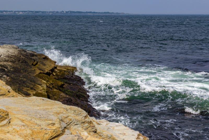 Waves crashing against rocky shore in Jamestown Rhode Island. Oeans waves splashing against rocks in Beavertail royalty free stock image
