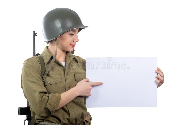 Η νέα γυναίκα έντυσε στην αμερικανική στρατιωτική στολή ww2 που παρουσιάζει κενή κενή πινακίδα στοκ φωτογραφίες με δικαίωμα ελεύθερης χρήσης