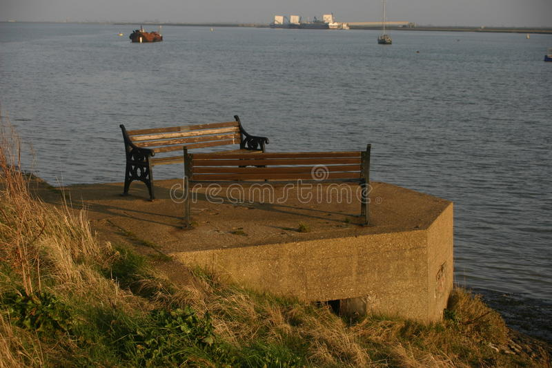 World War Two Pillbox with seats. A World War II pillbox by a river with seats on top. A novel use for a pillbox and certainly a good view over the river. Boats royalty free stock photography