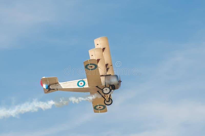 WW1 triplane. Historic WW1 British military triplane with dogfight damage smoke trail royalty free stock image