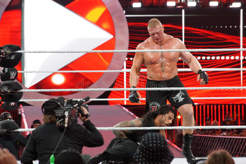 WWE Champion Brock Lesner bleeds from face as Roman Reigns holds stock photos