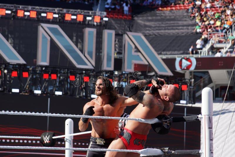 WWE-de Worstelaar Seth Rollins duwt Randy Orton in het hoekverstand stock afbeelding