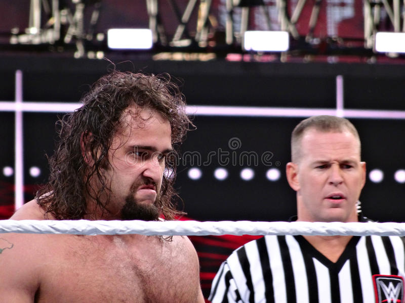 WWE Wrestler Rusev with mad face stands in ring next to ref. SANTA CLARA - MARCH 29: WWE Wrestler Rusev with mad face stands in ring next to ref during USA royalty free stock image