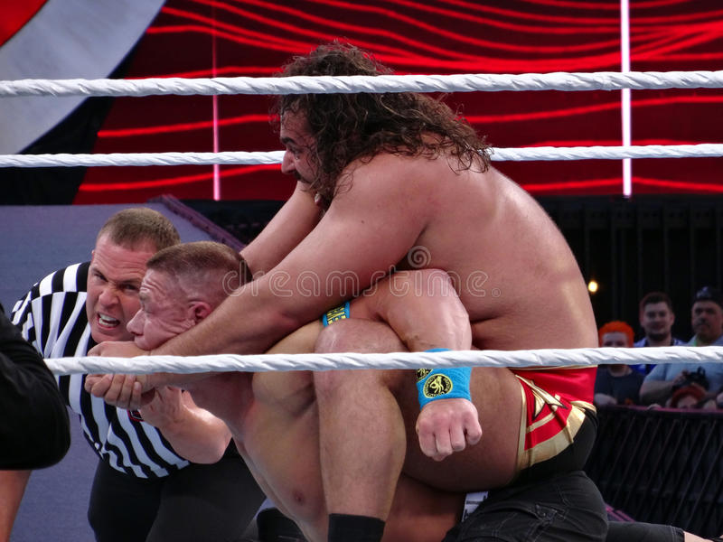 WWE Wrestler Rusev puts John Cena in The Accolade with ref chec. SANTA CLARA - MARCH 29: WWE Wrestler Rusev puts John Cena in The Accolade with ref checking in royalty free stock photography