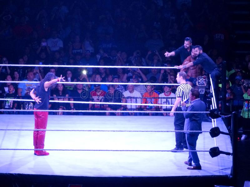WWE Wrestler Shinsuke Nakamura does pre-match ritual as Jinder Mahal stands in ring with The Singh Brothers. Honolulu - September 13, 2017: WWE Wrestler Shinsuke royalty free stock photography