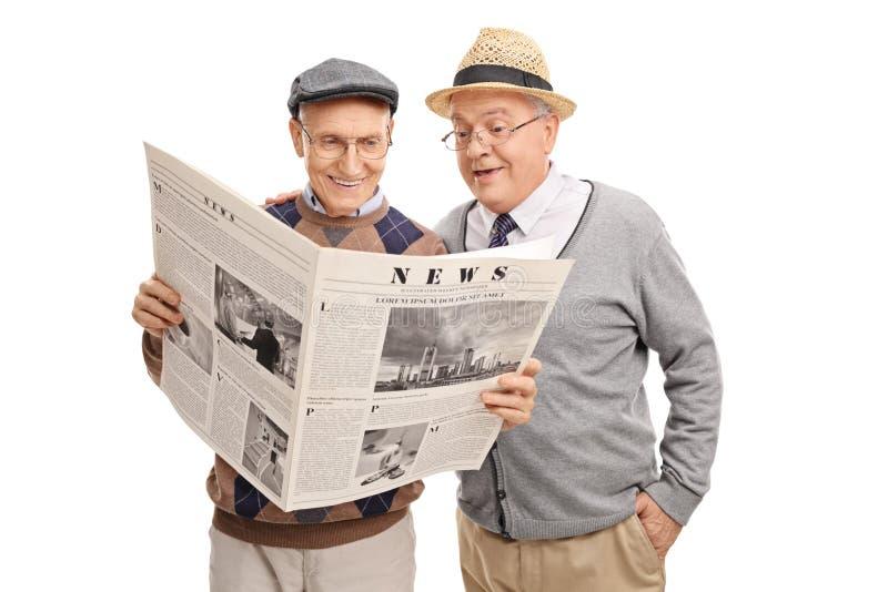 Wwo höga gentlemän som läser en tidning royaltyfri bild