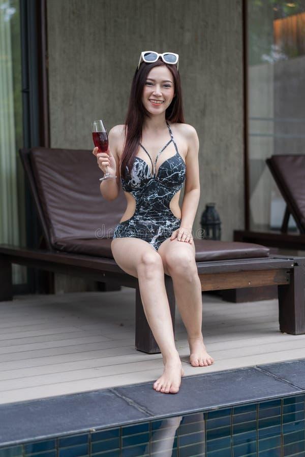 Wwoman на deckchair и держать стекло в бассейне стоковое изображение