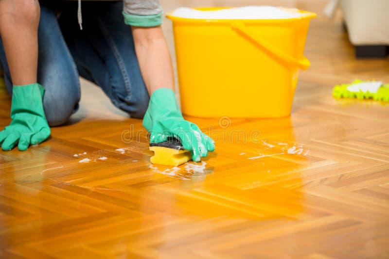 WWoman que limpia el piso mientras que se arrodilla fotos de archivo libres de regalías