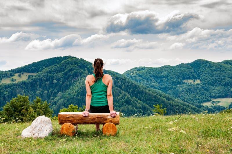 Wwoman que se sienta en un banco en las colinas foto de archivo