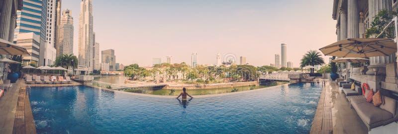 Wwoman relaksuje przy luksusowego wysokiego wzrosta pływackim basenem obrazy stock