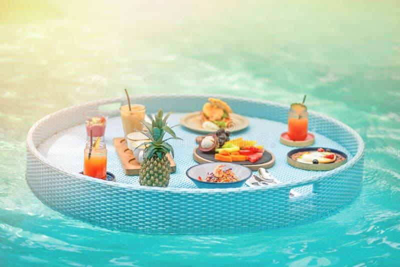 Wyśmienicie śniadanie na spławowym stole w basenie odcień iluminacje obraz royalty free