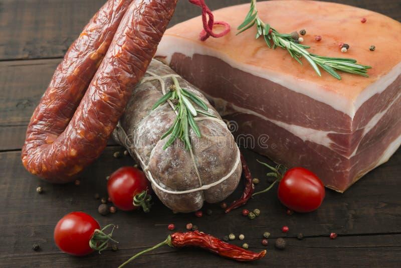 Wyśmienicie uwędzony kiełbasiany salami z pieprzem, pomidorami i rozmarynami na drewnianej desce, obraz royalty free