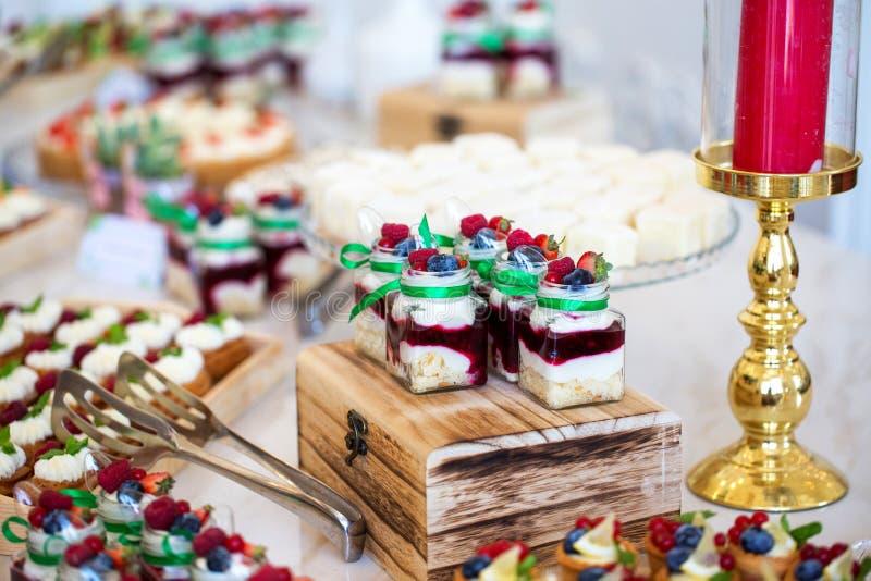 Wyśmienicie wesele cukierku baru deseru stół folował z tortami, cukierki i świeczki fotografia stock