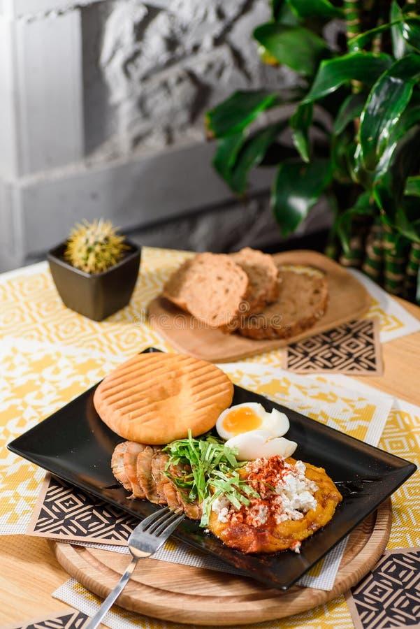 Wyśmienicie śniadanie z gotowanymi jajkami, chlebem na czarnym talerzu, dyniowym puree, sałaty, serowego i świeżego, zdjęcia royalty free