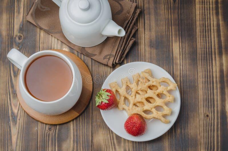 Wyśmienicie śniadanie z herbatą, opłatki dekorował z świeżą truskawką na drewnianym stole, odgórny widok obrazy stock