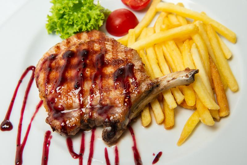 Wyśmienicie antrykot piec na grillu stek na bielu talerzu z francuzów dłoniakami i dekorującym z kumberlandem obrazy royalty free