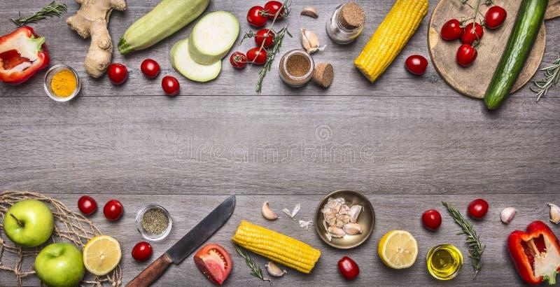 Wyśmienicie asortyment rolni świezi warzywa z nożem na popielatym drewnianym tle, odgórny widok Jarscy składniki dla gotować fotografia royalty free