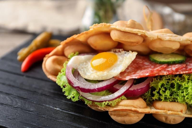 Wyśmienicie bąbla gofr z smażącymi jajka i kiełbasy plasterkami na drewnianej desce, zbliżenie zdjęcia royalty free