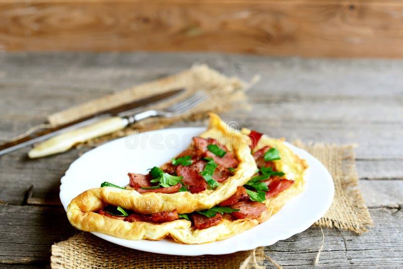 Wyśmienicie bekonowy omelette na talerzu Domowej roboty fałdowy omelette z smażącym bekonem dekorował z pietruszką Serdecznie jaj obraz stock
