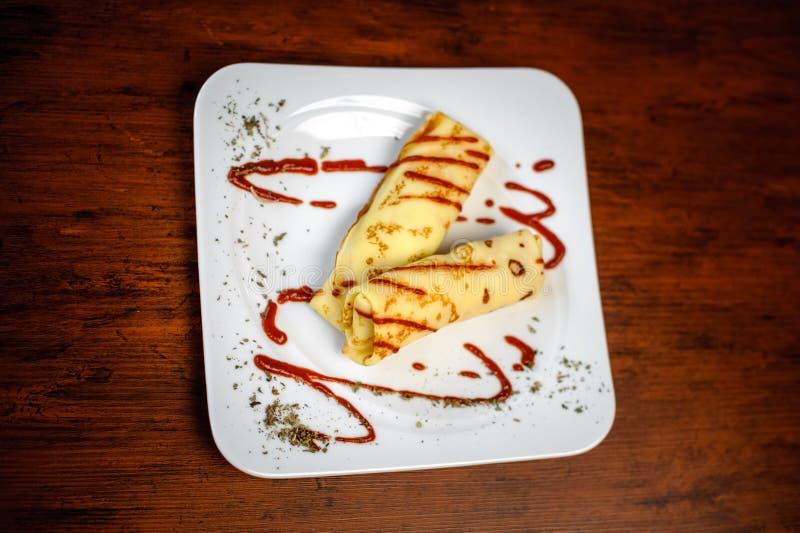 Wyśmienicie bliny z mięsem, pikantność i kumberlandem na białym talerzu, zdjęcie stock