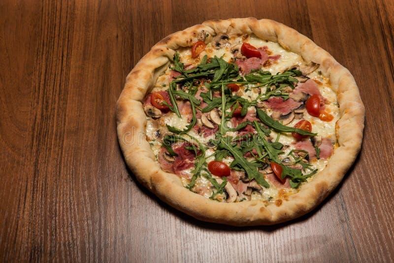 wyśmienicie cała pizza z arugula, baleronem, pieczarkami i pomidorami, obrazy stock