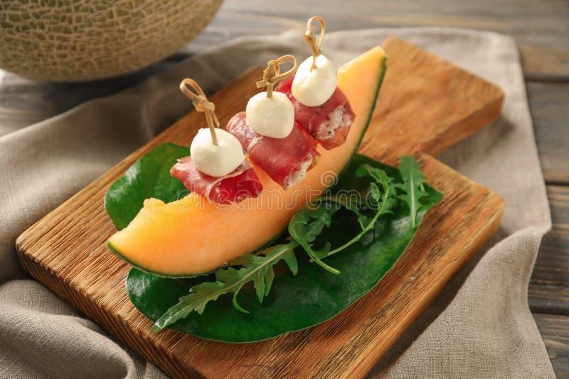 Wyśmienicie canape z melonem, prosciutto i mozzarellą na drewnianej desce, zdjęcia royalty free