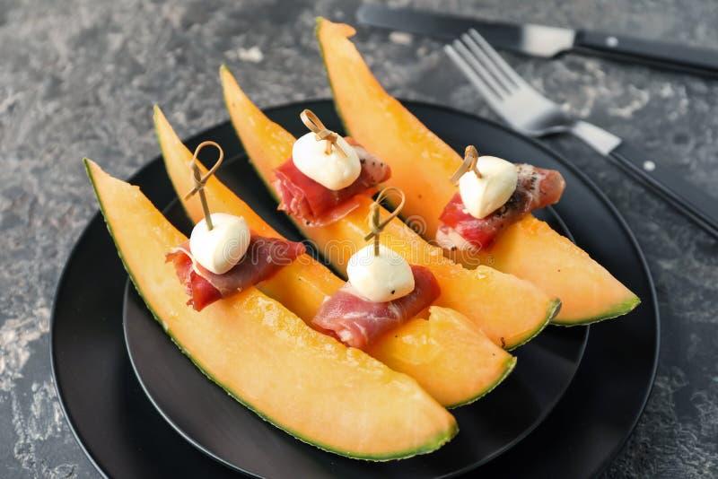 Wyśmienicie canape z melonem, prosciutto i mozzarellą na talerzu, zbliżenie fotografia stock