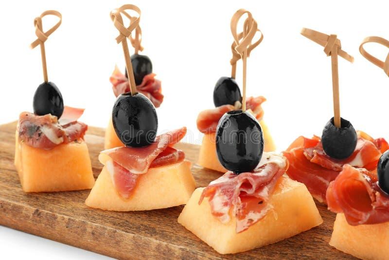 Wyśmienicie canape z melonem, prosciutto i oliwkami na drewnianej desce przeciw białemu tłu, zdjęcia stock