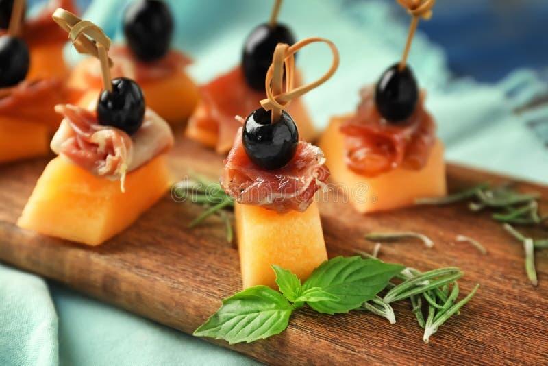 Wyśmienicie canape z melonem, prosciutto i oliwkami na drewnianej desce, zbliżenie obraz royalty free