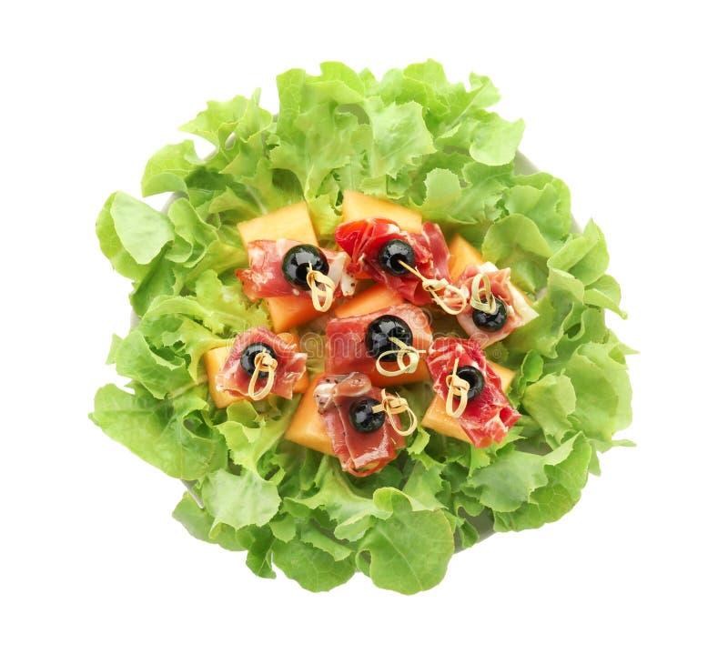 Wyśmienicie canape z melonem, prosciutto i oliwkami na sałacie, opuszcza przeciw białemu tłu fotografia royalty free