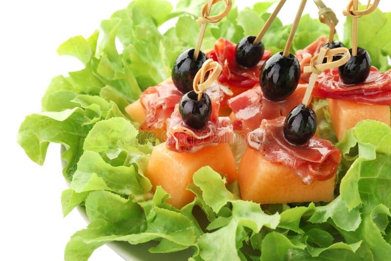 Wyśmienicie canape z melonem, prosciutto i oliwkami na sałacie, opuszcza, zbliżenie obrazy stock