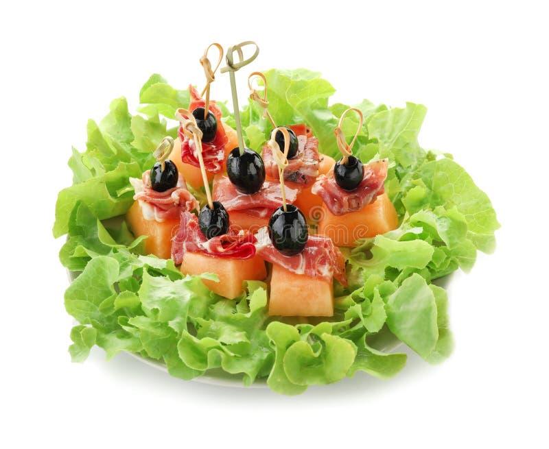 Wyśmienicie canape z melonem, prosciutto i oliwkami na talerzu przeciw białemu tłu, fotografia royalty free