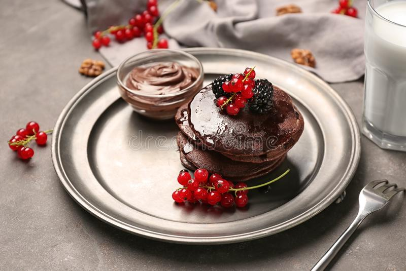 Wyśmienicie czekoladowi bliny dekorowali z jagodami i słodkim syropem na talerzu fotografia stock