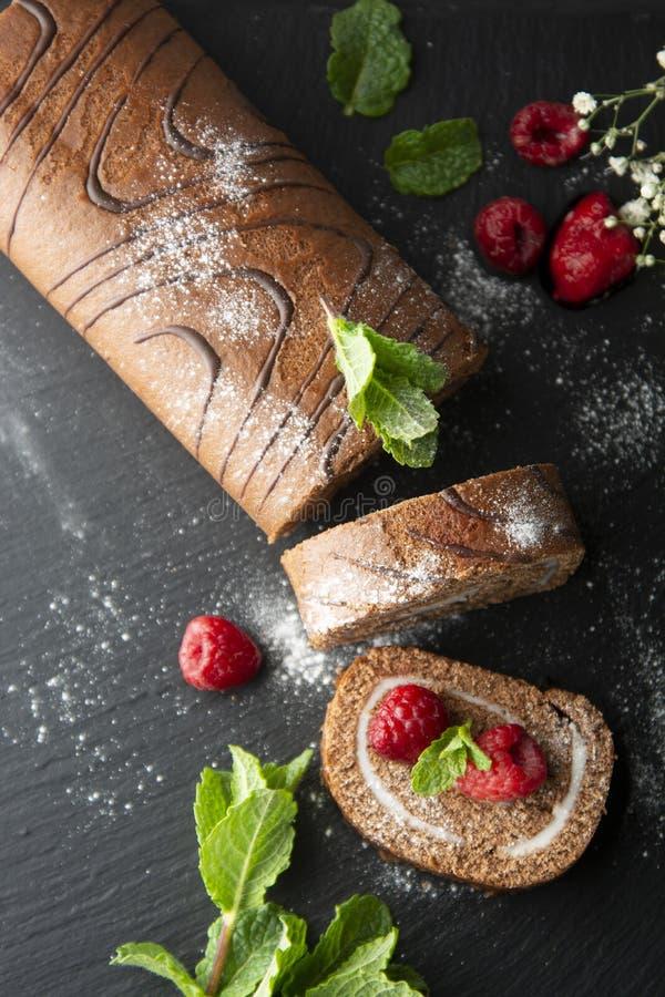 Wyśmienicie czekoladowy rolki gąbki tort z waniliową śmietanką i nowymi liśćmi Pustynny słodki jedzenie fotografia stock