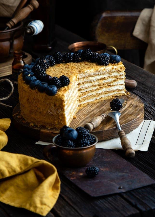 Wyśmienicie domowej roboty cięcie rosyjski miodowego torta medovik z białymi śmietanki, błękitnych i czarnych jagodami na w fotografia stock