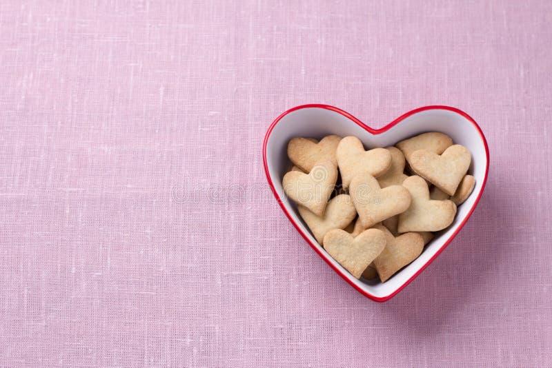 Wyśmienicie domowej roboty ciastek serca w czerwonym sercu kształtującym rzucają kulą dla walentynka dnia na różowym tekstylnym t zdjęcia royalty free