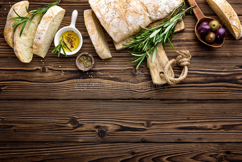 Wyśmienicie domowej roboty włoski ciabatta chleb z oliwa z oliwek i oliwkami na drewnianym nieociosanym tle nad widok, przestrzeń obraz royalty free